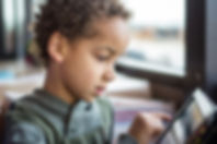 Young curly, brown haired boy playing on a tablet