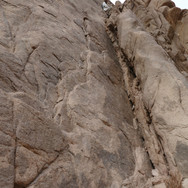 Hassan leads the way to the top of a steep, rocky crack on the side of the ravine.