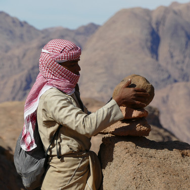 Small piles of stones called 'rujoom' are used to mark trails by the Bedouin. Each one is visible from the last & together they form a guiding line through a landscape. Rujoom might look fragile but if assembled correctly they stand up even in strong winds. Mohammed is adding a new one, making the route easier to follow.