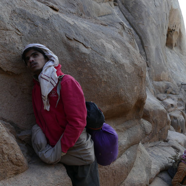 Omar rests below the summit. Hassan has wood strapped to this bag, ready for a cold night.