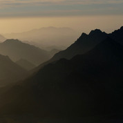 Jebel Um Anab seen in silhouette at dawn. It is a mountain with three separate pyramid peaks, each connected by a narrow ridge. The highest of the peaks reaches 1692m & it's the first of six mountains climbed on the RSMT.