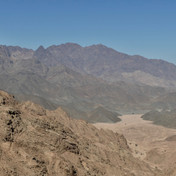 High, rugged passes are crossed as the trail runs south from Wadi Billi. Mohammed gazes back to the highlands of Jebel Abu Dukhaan.