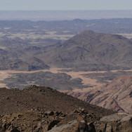 Wadi Ghuza divides the two great massifs of the Red Sea Mountains: Jebel Abul Hassan & Jebel Gattar. At the end it opens onto desert lowlands. Musallem is looking out over the lowlands to a faraway tableland called 'El Jilf'. On the other side of El Jilf is the green ribbon of Egypt's fabled Nile Valley.