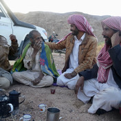 Almost every Bedouin family is known to every other one & Hassan is greeting old friends here. When visiting the Bedouin it helps to know a few basic dos and don'ts. The Bedouin usually sit in a circle, face to face. You should sit cross-legged or kneel & never show the soles of your feet to somebody: a mark of disrespect. One Bedouin handles the teapot & you should wait to be served. Tea is served to the person on the right first, then the next on the right and so on, around the circle. This custom is upheld even if a king is to the left. The Bedouin follow their traditions in serving guests, never a rank or title. One guest is never made to feel more or less than the next. A guest is a guest for the Bedouin. Who it is doesn't matter. An old Bedouin proverb instructs hosts to 'Serve coffee to the right, even if Abu Zeid is to the left'. Abu Zeid was a tribesman of the Bani Hilal & the greatest of all Bedouin heroes, whose life is still narrated in fireside legends today.