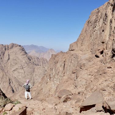 Mohammed at the top of a high ravine, nearing the upper parts of the Jebel Gattar massif.