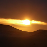 The sun sinks behind low hills around Jebel Nasb Umsayri, climbed at the beginning of day three.