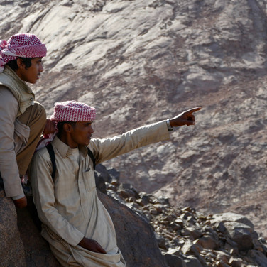Gullies lead to a ridgeline which is followed upwards. Views open over the desert & Mohammed is pointing out faraway places to Musallem here.