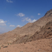 Hassan leads the way over low passes, moving into rugged desert lowlands.