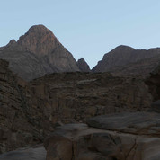 Dusk draws in as the trail winds down steep, rugged cliffs to the lower wadis of Jebel Gattar.