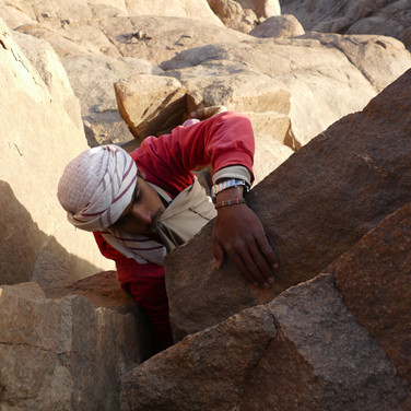 Getting onto the highest summit involves a short, vertical step of climbing. Omar holds the skirt of his jelebeya in his teeth, making sure it doesn't catch as he pulls himself onto the top.