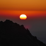 Hikers wake on Jebel Shayib's 2187m summit as the sun rises over the waters of the Red Sea.