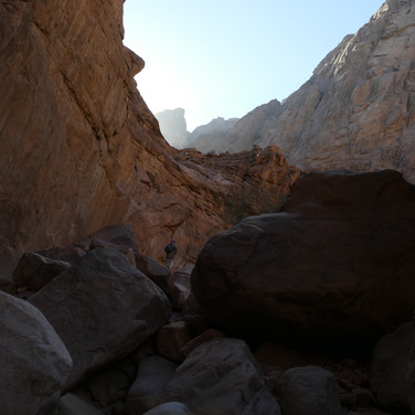 Jebel Gattar is one of the great crown jewels of the Middle East's mountains: a vast wilderness of jagged peaks & pinnacles, deep, shadowy ravines & dripping springs. The trail leads out of Wadi Ghuza & into Jebel Gattar's remote highlands through this red gorge. Mohammed leads ahead, weaving through boulders.