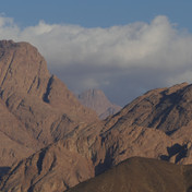 The trail leads north out of the red rock wilderness of Jebel Gattar: spectcular peaks tower high on every side, touching the early morning clouds.