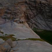 Deep green pools gather in the wadi below the dripping spring of El Nagaata.