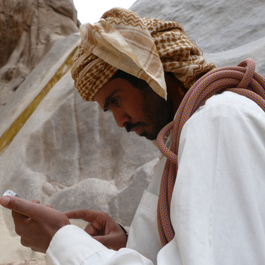 We introduced Hassan Abu Musallem on day 7. He's a head guide on the RSMT & one of the Maaza's finest mountain men. He lives at the foot of Jebel Shayib & has walked the mountain widely since his childhood, exploring its crags from every side. A short rope is slung over his shoulder, ready to protect any tricky steps. The RSMT's other head guide Mohammed Muteer & young cameleer Musallem Mahmoud go a different way, escorting the camels over easy passes to a rendezvous where they will wait for hikers to descend.