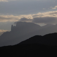 The trail continues into the foothills of Jebel Abu Dukhaan. Clouds gather behind on Jebel Gattar.