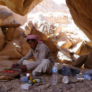 Mohammed shelters from the afternoon sun in a cave, cutting vegetables for lunch. Ancient pottery is found here showing the cave has been used as a refuge for many centuries.