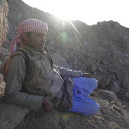 The first objective of the second day is Jebel Um Anab. The trail starts steeply, up rugged slopes. Here's Bedouin guide Mohammed Muteer taking a break in the early morning light.
