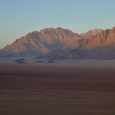 The Plain of Graygar rises north to the foothills of Jebel Shayib. Shadows of the nearby mountains grow slowly over the plain in the late afternoon.