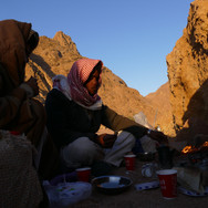 We wake deep in the wild, westerly parts of the Red Sea Mountains on day 5. The desert dawn is cold in spring but a warm fire & cup of Bedouin tea is usually enough of a draw for hikers to get out of their sleeping bags. Head guide Mohammed Muteer sits at the fire's edge & is making the tea.