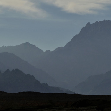 Jebel Shayib towers high in the morning haze. An early start is essential on the ascent day.