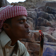 Mohammed lighting a cigarette, the Bedouin way.