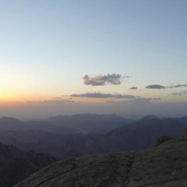 Omar takes a summit selfie in the last light.