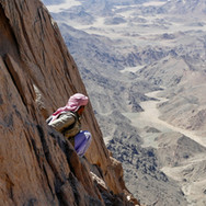 Getting onto Jebel Um Anab's high ridge involves an intricate scramble through steep cliffs. Here's Mohammed on the final part of the scramble, gazing down to winding wadis below.