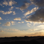 Clouds dot the sky as the sun sets & the mountains are reached west of the Plain of Graygar.