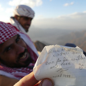 Hassan leafs through messages in the summit box, finding one written back in 1999.