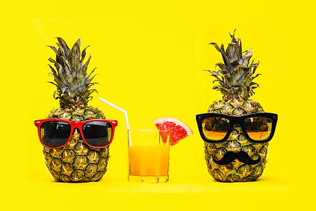 Two Fun Fashion pineapples with sunglasses and mustache with fresh tropical cocktail with fruit over