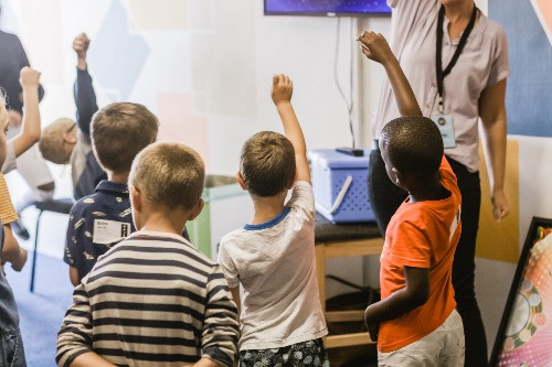 Young children keen to answer a question in class
