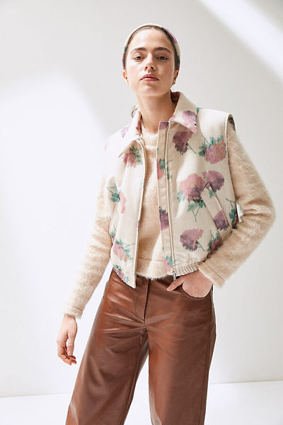 model wearing rose printed bodywarmer over wool knit and leather trousers