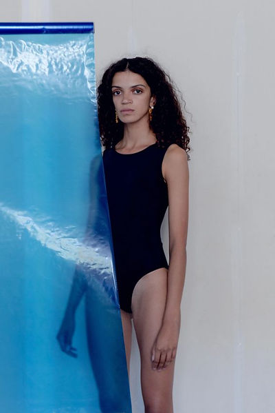 model  standing behind blue see through screen wearing high neck bathing suit