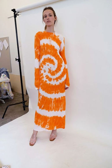 model wearing orange longsleeve dress with tie dye print from ethical fashion brand Nomia