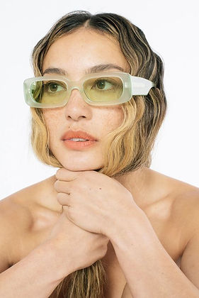 model with long wavy hear wearing mint green rectangular sunglasses with tinted glasses from ethical sunglass brand Bonnie Clyde