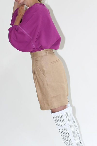 beige shorts worn with pink 80s sweater and high white perforated leather knee boots