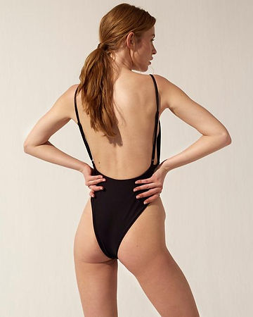 model wearing high legged black bathing suit with high