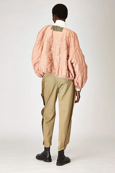 model from the back wearing pink short sustainable parka, camel pants and black leahter military boots AW21 fall 21