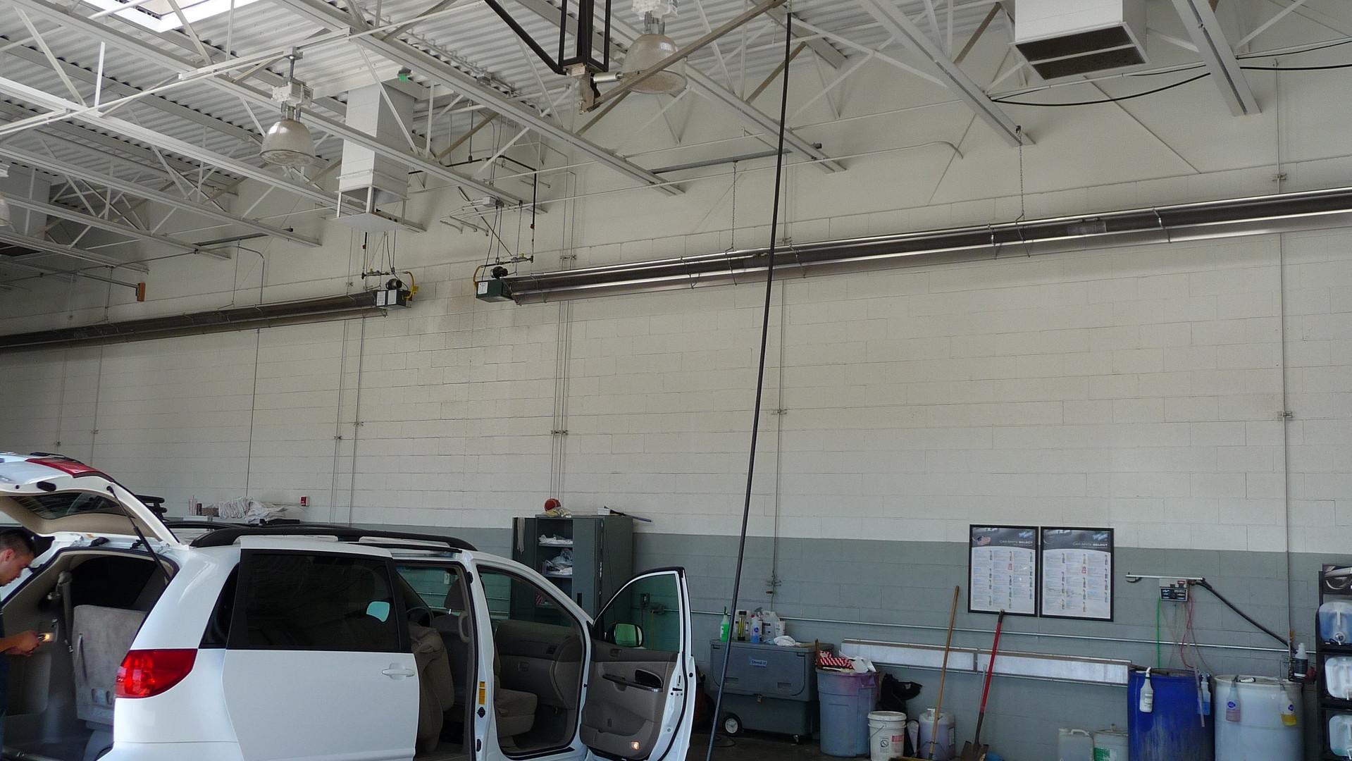 Auto detail bay with tube heater reflectors turned inward
