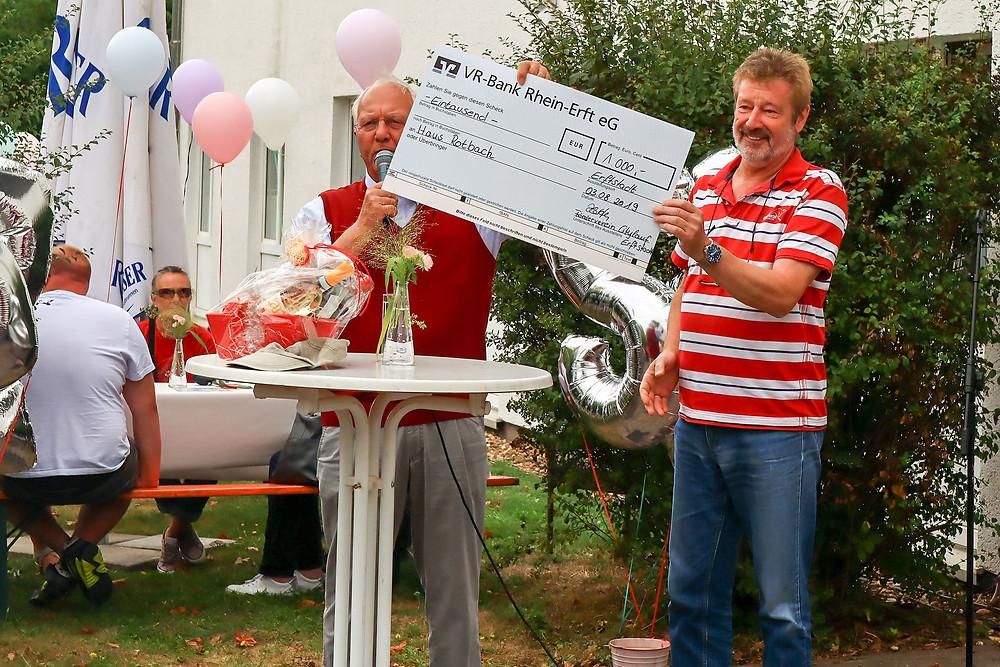 Adi Bitten übergibt einen symbolischen Scheck von 1000 €