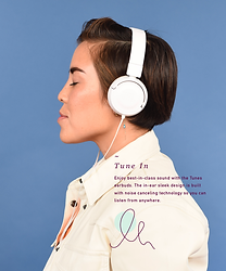 Side view of a woman wearing headphones and listening to music.