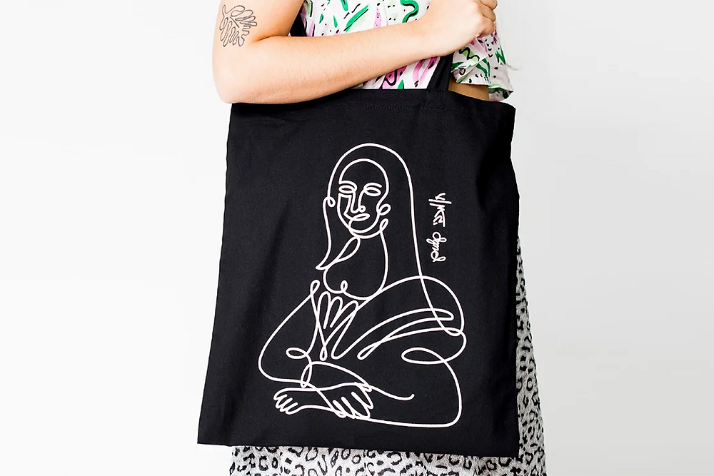 A tote bag with a graphic line illustration inspired by the Mona Lisa