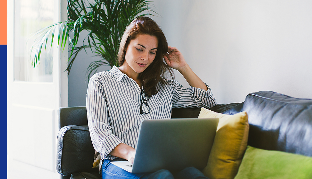 A woman sitting on a couch working remotely