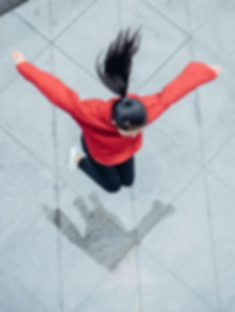 Picture of a girl with long black hair jumping in the air.