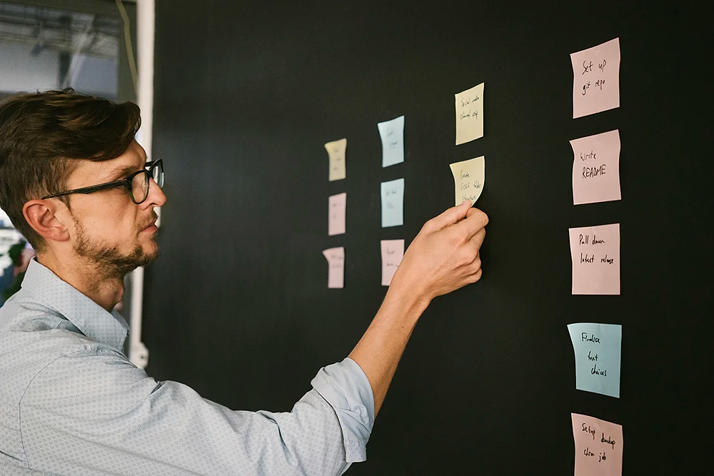 A person using sticky notes at work: The UX design process