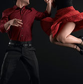 swing dancing couple - man with red shirt and woman with polka dot skirt leaping
