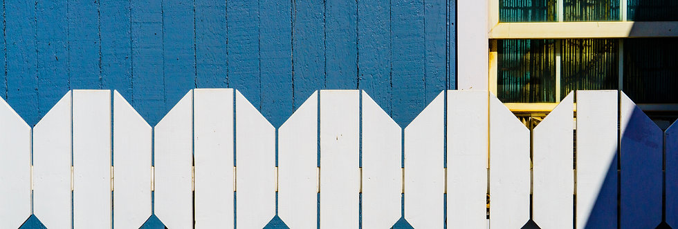 White picket fence in front of blue house and window