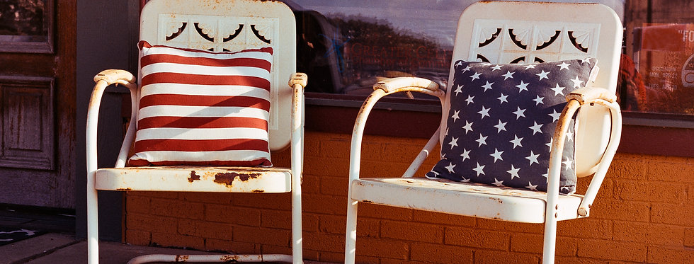 Old rocking chairs with red, white, & blue pillows