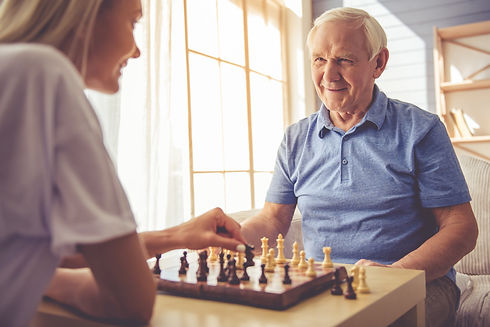 Beautiful young girl-volunteer and handsome old man are playing chess and smiling.jpg